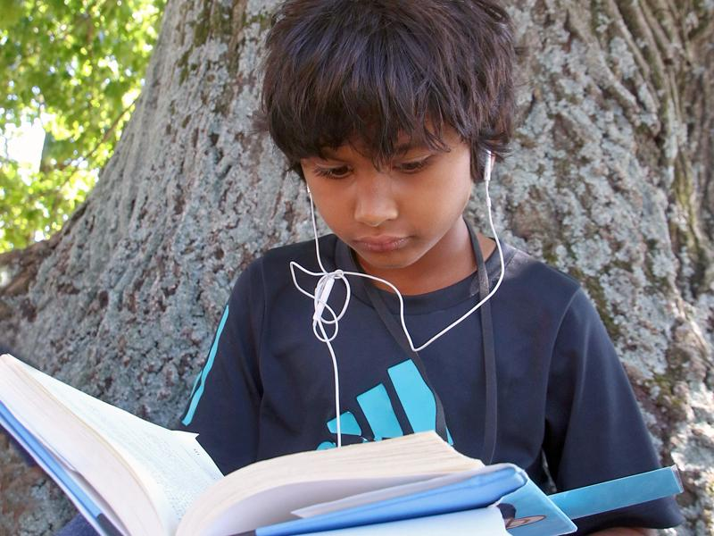 Columbus Academy student reading by tree